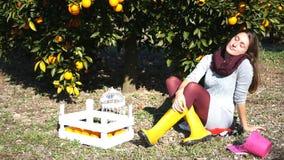 Mooie meisjeszitting onder de oranje boom stock videobeelden