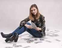 Mooie meisjeszitting op de rekeningen van het vloergeld Royalty-vrije Stock Afbeeldingen