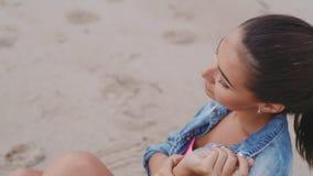 Mooie meisjeszitting op de zandige kust stock footage