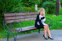 Mooie meisjeszitting op een bank in het park royalty-vrije stock foto's