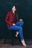Mooie meisjeszitting op een stoel Stock Afbeeldingen