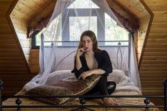 Mooie meisjeszitting op het bed stock afbeelding