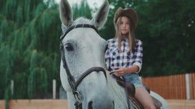 Mooie meisjeszitting op het paard en het glimlachen bij camera in 4K stock videobeelden