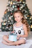 Mooie meisjezitting dichtbij de Kerstboom Stock Foto