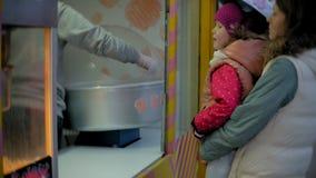 Mooie meisjezitting op een bank in een pretpark, die roze zoete gesponnen suiker eten die op rolschaatsen rollen stock footage