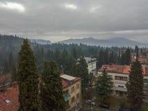 Mooie mening van de stad bij de voet groene nevelige bergen tegen bewolkte hemel royalty-vrije stock fotografie