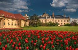 Mooie mening van het Tsjechische kasteel Lednice, met een bewolkte daverende hemel en heel wat rode tulpen Stock Foto