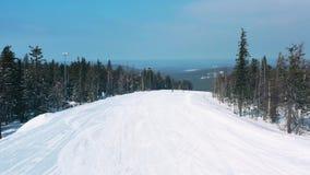 Mooie mening van mensen op een skihelling die van een spoor dichtbij naaldbomen in de winter tegen blauw beginnen te dalen stock video