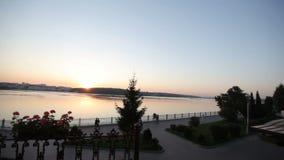Mooie meningen van het meer en de waterkant bij zonsondergang De mensen lopen op de schilderachtige dijk bij zonsondergang stock video