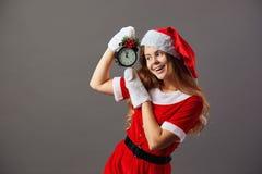 Mooie Mevr Santa Claus gekleed in de de rode robe, hoed van de Kerstman en de witte handschoenen houdt een klok die vijf aan toon royalty-vrije stock afbeeldingen