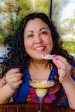 Mooie Mexicaanse vrouw die een heerlijk vanille en karamelroomijs in een terras van een cafetaria genieten van stock fotografie