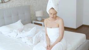 Mooie midden oude die blondevrouw in handdoek het witte handdoek lopen wordt verpakt stock video