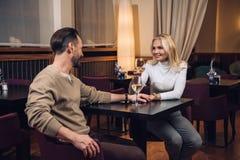 mooie midden oude paar het drinken wijn en het glimlachen van elkaar in hotelrestaurant stock afbeeldingen