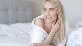 Mooie midden oude vrouw die bij het bed, het dragen van wit overhemd en het glimlachen liggen stock footage