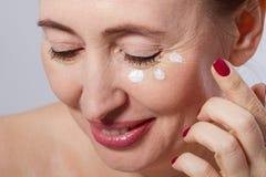 Mooie midden oude vrouw die kosmetische roombehandeling op gezicht op grijze achtergrond toepassen Spot omhoog en exemplaarruimte Royalty-vrije Stock Foto