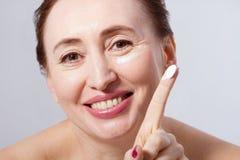 Mooie midden oude vrouw die kosmetische die roombehandeling op gezicht toepassen op grijze achtergrond wordt geïsoleerd Spot omho Stock Foto