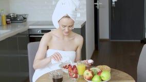 Mooie midden oude vrouwenzitting in haar keuken in de ochtend stock video