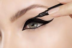Mooie model het van toepassing zijn eyelinerclose-up op oog Royalty-vrije Stock Afbeelding