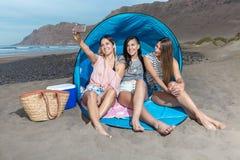Mooie modellen die voor selfie op strand stellen stock foto