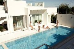 Mooie modellen in zwempak, die dichtbij luxueuze het zwemmen poo stellen royalty-vrije stock afbeeldingen