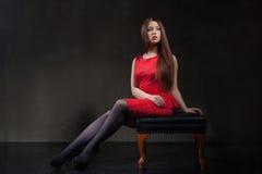 Mooie modelzitting op stoel in studio Stock Foto's