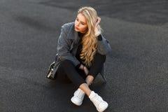 Mooie modieuze jonge modelvrouw in een modieuze grijze laag stock fotografie