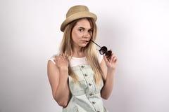 Mooie modieuze jonge vrouw in grijze denimkleding, een hoed en een zon stock fotografie