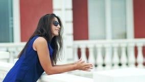 Mooie modieuze jonge vrouw in zonnebril die zich bij balkonluxe hotel of de bouw bevinden stock video