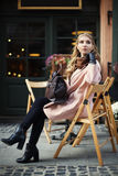 Mooie modieuze jonge vrouwenzitting in straatkoffie De Levensstijl van de stad Vrouwelijke manier Volledig lichaamsportret stock afbeelding