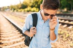Mooie modieuze kerel met glazen die, die op de treinsporen bij zonsondergang stellen, en op de telefoon spreken, hipster stellend Royalty-vrije Stock Foto