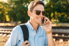 Mooie modieuze kerel met glazen die, die op de treinsporen bij zonsondergang stellen, en op de telefoon spreken, hipster stellend Royalty-vrije Stock Fotografie