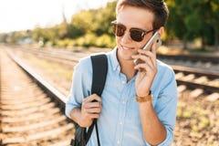 Mooie modieuze kerel met glazen die, die op de treinsporen bij zonsondergang stellen, en op de telefoon spreken, hipster stellend Stock Foto