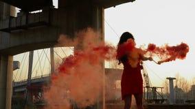 Mooie modieuze vrouw in rode kledingsdans met rode rook in slowmotion stock videobeelden
