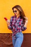 Mooie modieuze vrouwen met smartphone en hoofdtelefoons Vliegende haren Oranje Achtergrond Exemplaar-ruimte Royalty-vrije Stock Afbeeldingen