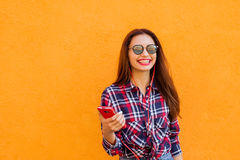 Mooie modieuze vrouwen met smartphone en hoofdtelefoons Vliegende haren Oranje Achtergrond Exemplaar-ruimte Stock Afbeeldingen