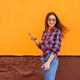 Mooie modieuze vrouwen met smartphone en hoofdtelefoons Vliegende haren Oranje Achtergrond Exemplaar-ruimte Royalty-vrije Stock Foto