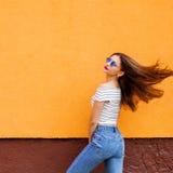 Mooie modieuze vrouwen Vliegende haren Oranje Achtergrond Exemplaar-ruimte Stock Fotografie