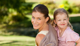 Mooie moeder die dochter een vervoer per kangoeroewagen geeft stock afbeelding