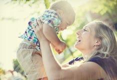 Mooie Moeder die haar aanbiddelijke babyjongen in het zonsondergangzonlicht houden royalty-vrije stock afbeeldingen