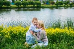 Mooie moeder die haar zoon in het park van de de zomerstad omhelzen royalty-vrije stock afbeelding
