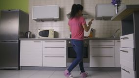 Mooie moeder die met gelukkige baby in keuken dansen stock videobeelden