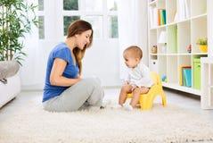 Mooie moeder die weinig kind hoe te zitting op onbenullig leren stock afbeelding