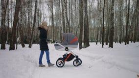 Mooie moeder duwende kinderwagen in het de winterpark stock videobeelden