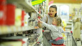 Mooie Moeder en Dochter binnen Hypermarket die Één of andere Rode Pan kiest en het zet in Boodschappenwagentje stock videobeelden