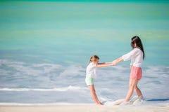 Mooie moeder en dochter die bij Caraïbisch strand de zomer van vakantie genieten Familie die op tropische beroemde heel baai lope royalty-vrije stock fotografie