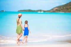 Mooie moeder en dochter die bij Caraïbisch strand de zomer van vakantie genieten Familie die op tropische beroemde heel baai lope royalty-vrije stock afbeelding