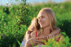 Mooie moeder en dochterzitting op gras Royalty-vrije Stock Afbeelding