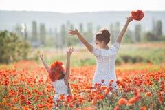 Mooie moeder en haar dochter die op het gebied van de de lentebloem spelen royalty-vrije stock fotografie