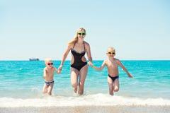 Mooie moeder en twee mooie handen die van de zoonsholding op de golven lopen Pret, familie-vriendschappelijke de zomervakantie stock afbeelding