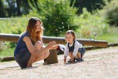 Mooie moeder en weinig dochter op speelplaats Stock Afbeeldingen